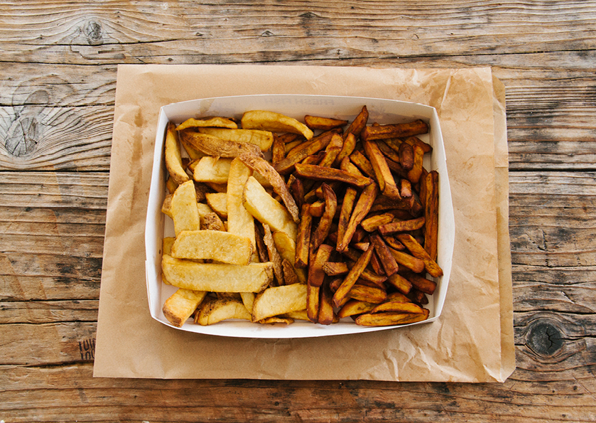 A two-page spread of a photograph of an order of hot chips on a wooden table