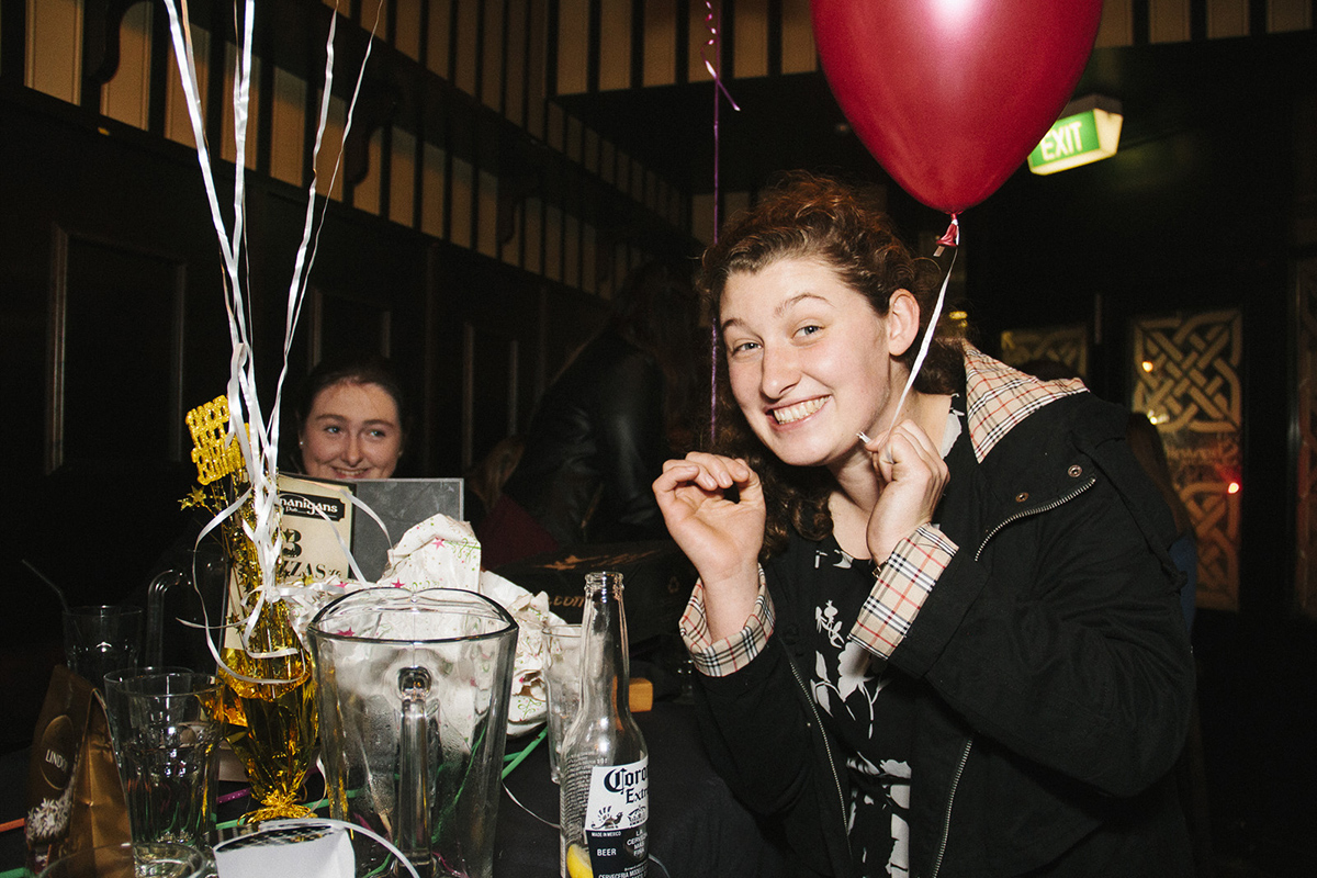 A photograph of two people at a birthday party, one of them is holding onto a helium balloon and smiling at the camera