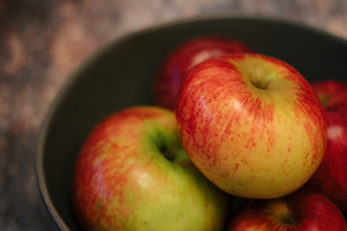 A photograph of a collection of apples in a dark bowl